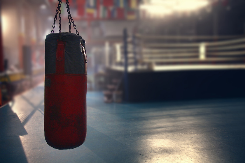 Red and black punching bag hanging in a empty gym with a boxing ring in the background