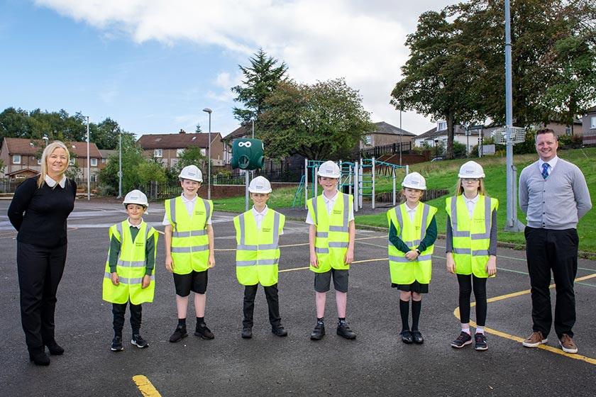 Children from Bushes Primary School wearing high visibility jackets and hard hats running across the playground