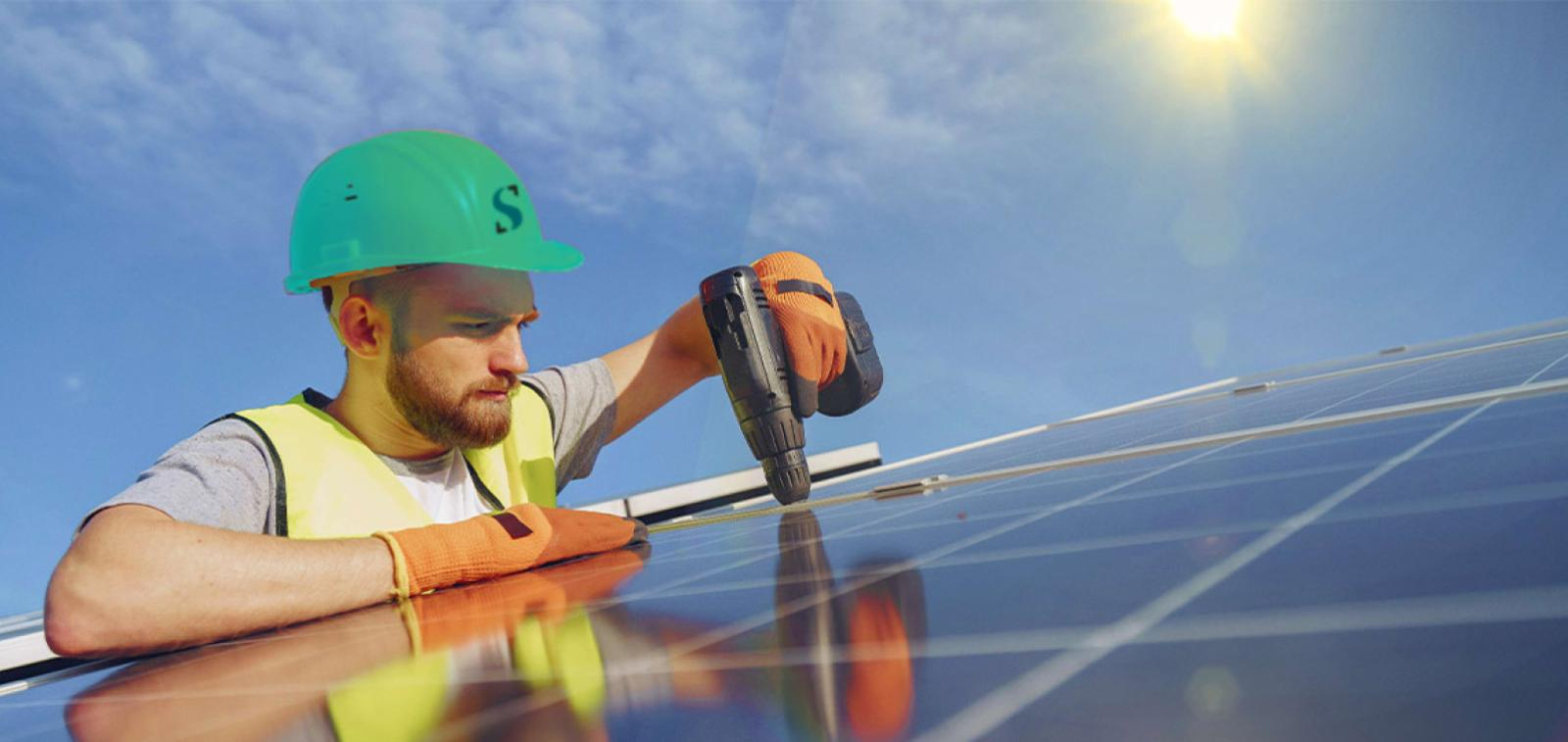 A workman wearing a Sanctuary branded hard-hat carries out maintenence on a solar panel