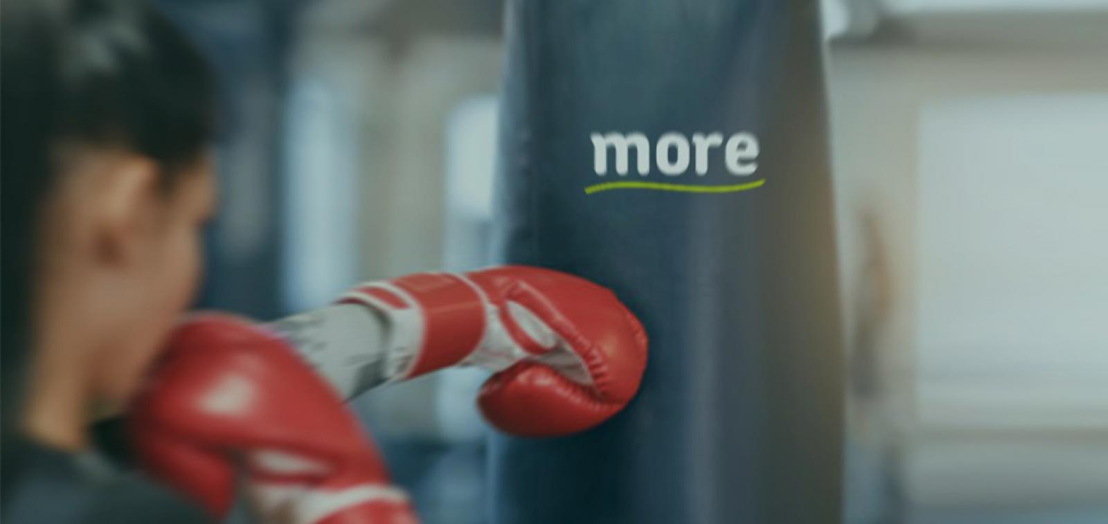 Woman wearing boxing gloved punching a black punching bag with the Sanctuary Homes MORE! logo on