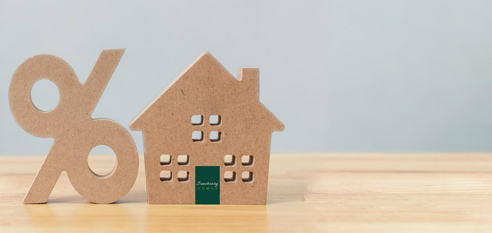 A cardboard cut out of a percentage symbol and a house with the Sanctuary Homes logo on it on a wooden table