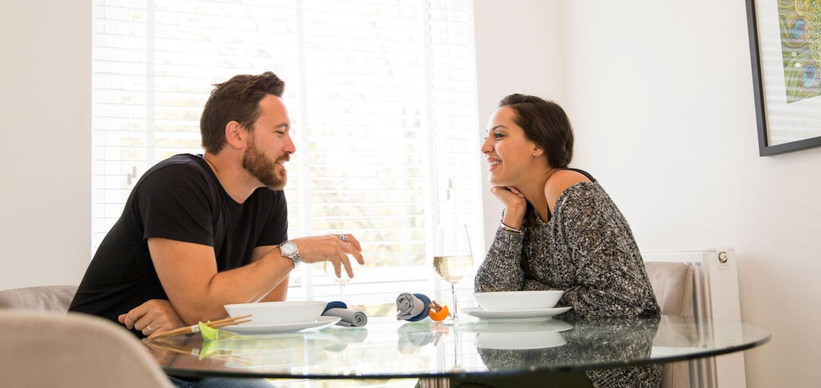 A couple enjoy a meal together after moving into their first home through a shared ownership scheme.