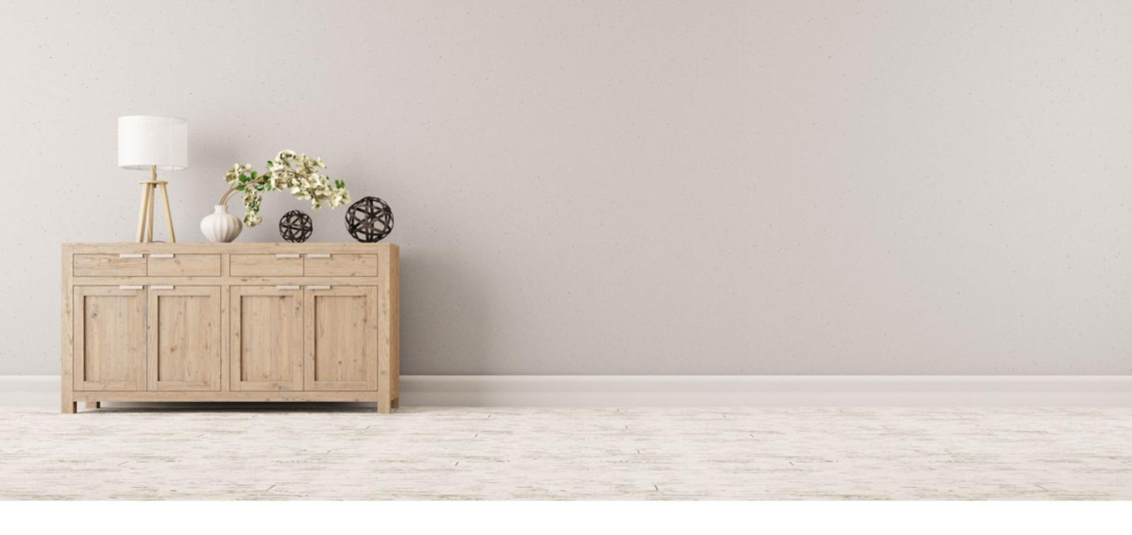 A chest of drawers with a lamp against a grey wall.