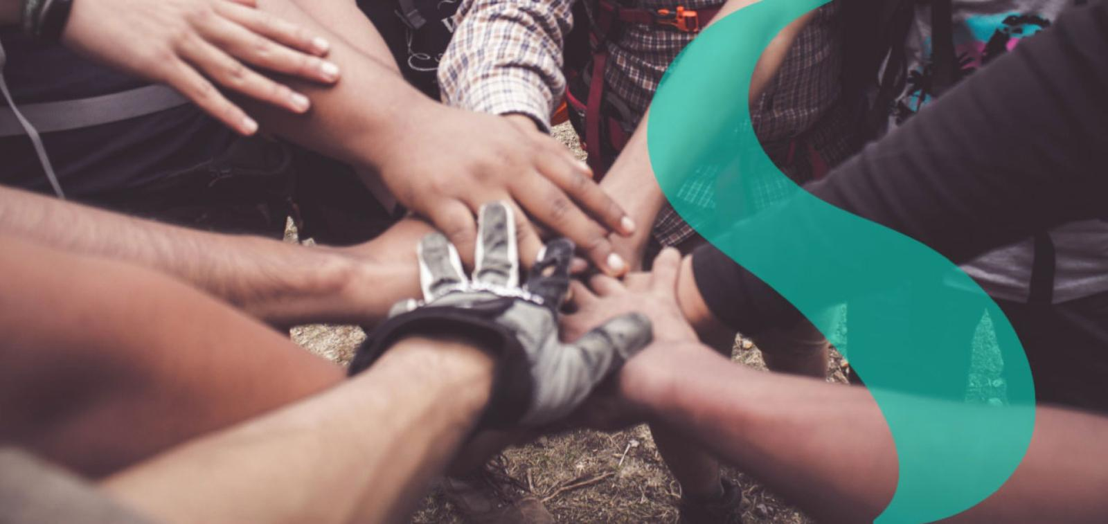 A group of hands piled on top of each other.